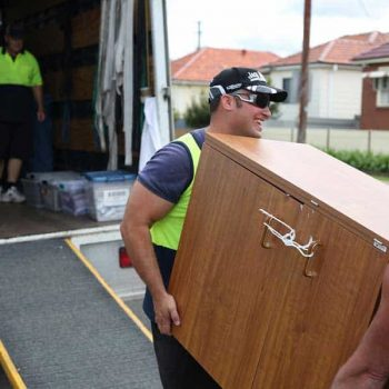 Two professional movers team up to lift a heavy cabinet down a moving truck ramp.