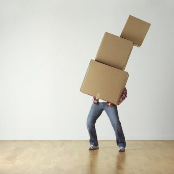 Man struggling to move boxes
