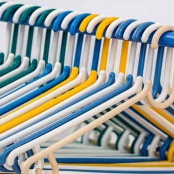Multi-colored clothes hangers in packed closet