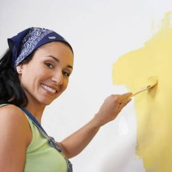 Woman painting new home after moving in fort worth