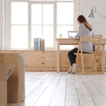A girl sits at a desk researching Denton TX moving companies.
