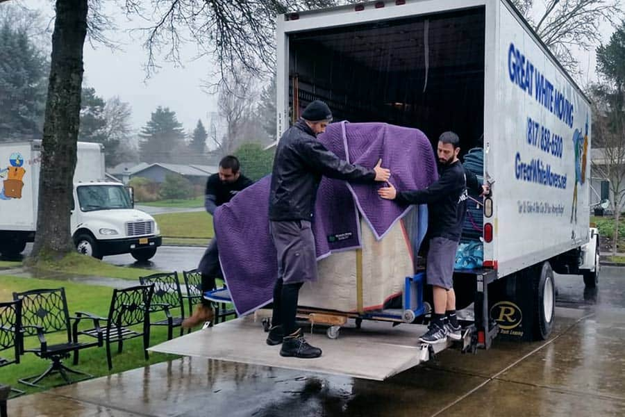 Movers moving furniture in the rain