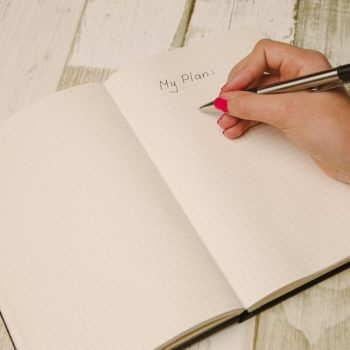 Person writing a plan in a notebook