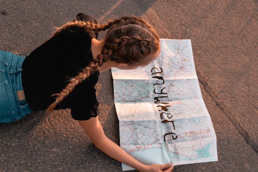 "Girl reading a paper map with ""anywhere"" written on it"