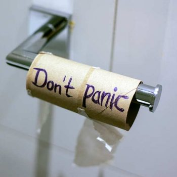 """Empty toilet paper roll with the words """"don't panic"""" written"""