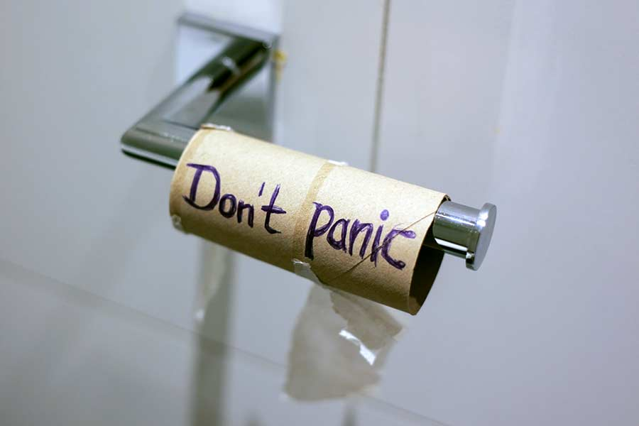 "Empty toilet paper roll with the words ""don't panic"" written"