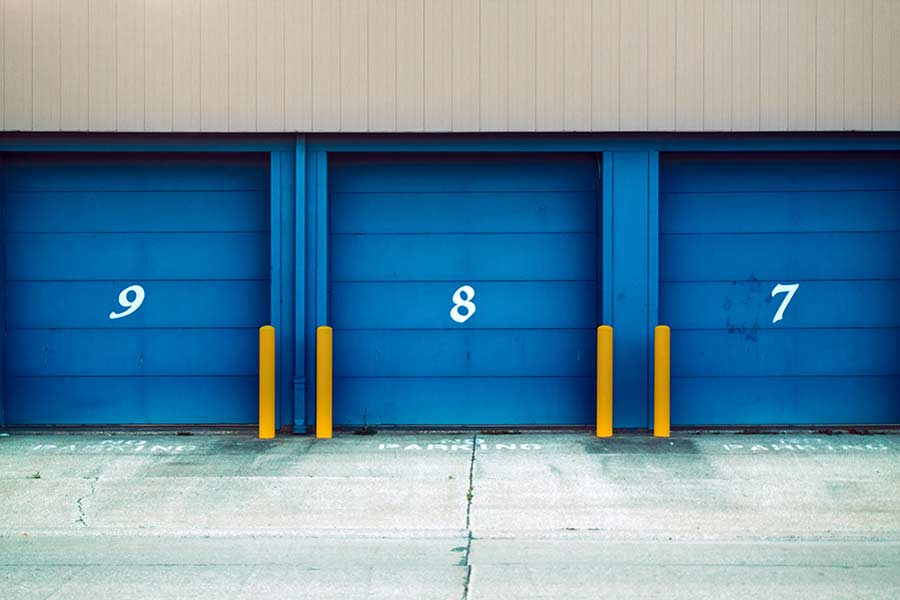 A row of numbered storage units with blue doors