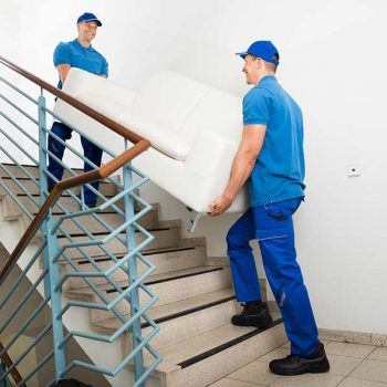 Professional movers carrying a sofa up a flight of stairs