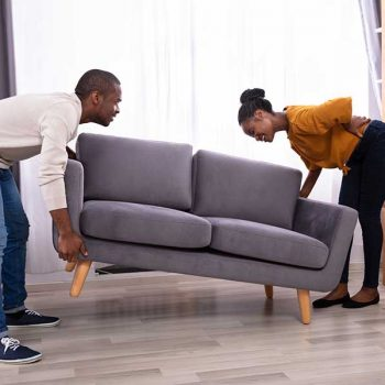 Woman holding her back while trying to lift a heavy couch with her husband